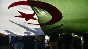 Algerian demonstrators wave the national flag during a demonstration in the capital Algiers, on February 28, 2020. Mass protests erupted in Algeria a year ago last Saturday, in response to President Abdelaziz Bouteflika announcing he intended to run for a fifth term after 20 years in power -- despite being debilitated by a 2013 stroke.