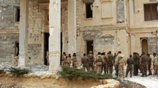 Des soldats de l'armée syrienne se tiennent devant un palais de la famille royale qatarie, à proximité de la cité antique de Palmyre, , jeudi 24 mars 2016.