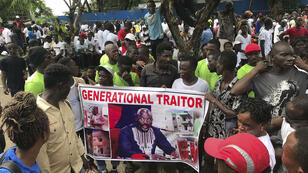 Los manifestantes sostienen un cartel que muestra al presidente de Liberia, George Weah, mientras se reúnen frente a la Mansión de Liberia, en Monrovia, el 7 de junio de 2019, durante una marcha antigubernamental en protesta de la inflación y la corrupción.