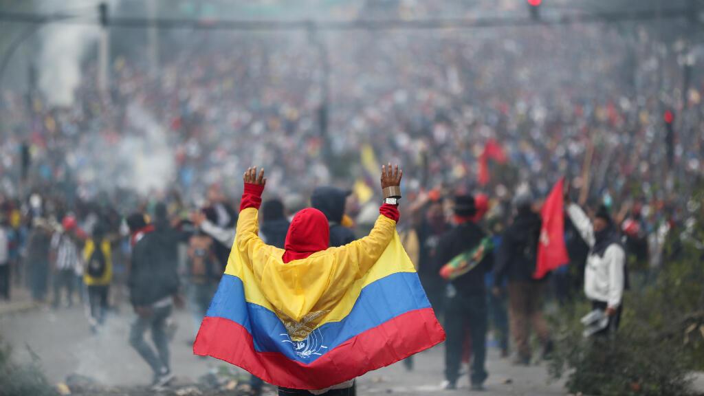 Un manifestante cubierto con una bandera ecuatoriana reacciona durante una protesta contra las medidas de austeridad del presidente de Ecuador, Lenín Moreno, en Quito, Ecuador, el 8 de octubre de 2019.
