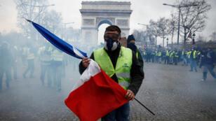 Un manifestante de los 'chalecos amarillos' porta una bandera de Francia mientras camina entre gases lacrimógenos en la avenida de los Campos Elíseos en París, el 8 de diciembre de 2018.