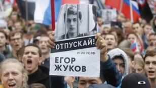 Un supporter de l'étudiant et blogueur Yegor Zhukov, emprisonné après une manifestation, brandit une pancarte dénonçant l'exclusion des candidats de l'opposition des élections locales, le 10 août 2019.