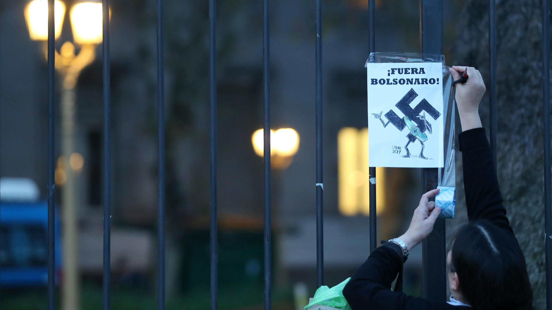 """Un residente instala un cartel que dice """"Fuera Bolsonaro"""", durante una protesta contra el presidente de Brasil por su visita a Buenos Aires, Argentina, el 6 de junio de 2019."""