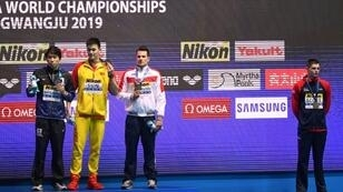 Worlds apart: Briton Duncan Scott (far right) snubs gold medallist Sun Yang (in yellow) after the 200m freestyle final on Tuesday night