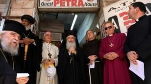 Greek Orthodox Patriarch of Jerusalem Theophilos III (C) stands with other Christian leaders for prayer outside a hostel near Jaffa Gate in Jerusalem's Old City on July 11, 2019