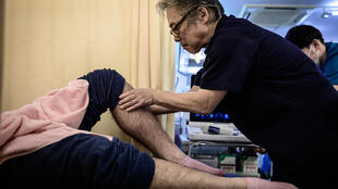 Hiroyuki Mitsuhashi, who uses 'judo therapy', treats a rugby player at his Tokyo clinic