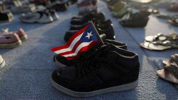 Una bandera de Puerto Rico es puesta en un par de zapatos como cientos de zapatos que se muestran en el Capitolio para rendir homenaje a las víctimas del huracán María.