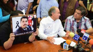 Un colega de Daniel Esqueda sostiene una foto de su compañero durante una rueda de prensa ofrecida por Juan Manuel Carreras, gobernador de San Luis Potosí