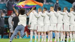 Une personne brandissant  un grand drapeau arc-en-ciel pendant l'hymne hongrois avant le match de l'Euro Allemagne-Hongrie le 23 juin 2021 à Munich