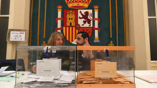 Two workers are seen during general election in Madrid on November 10, 2019.
