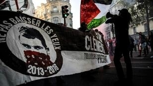 Demonstrators hold a banner sporting the image of killed anti-fascist protestor Clement Meric