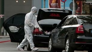 Angelos Tzortzinis, AFP | Forensic experts of the police search for evidence in and around the car of Greek former prime minister Lucas Papademos in Athens on May 25, 2017, after Papademos was hurt when an explosive device went off inside his car.