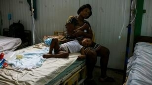 A young patient lies on his mother's lap at the postoperative ward during a doctors' strike at the public hospital in Port-au-Prince