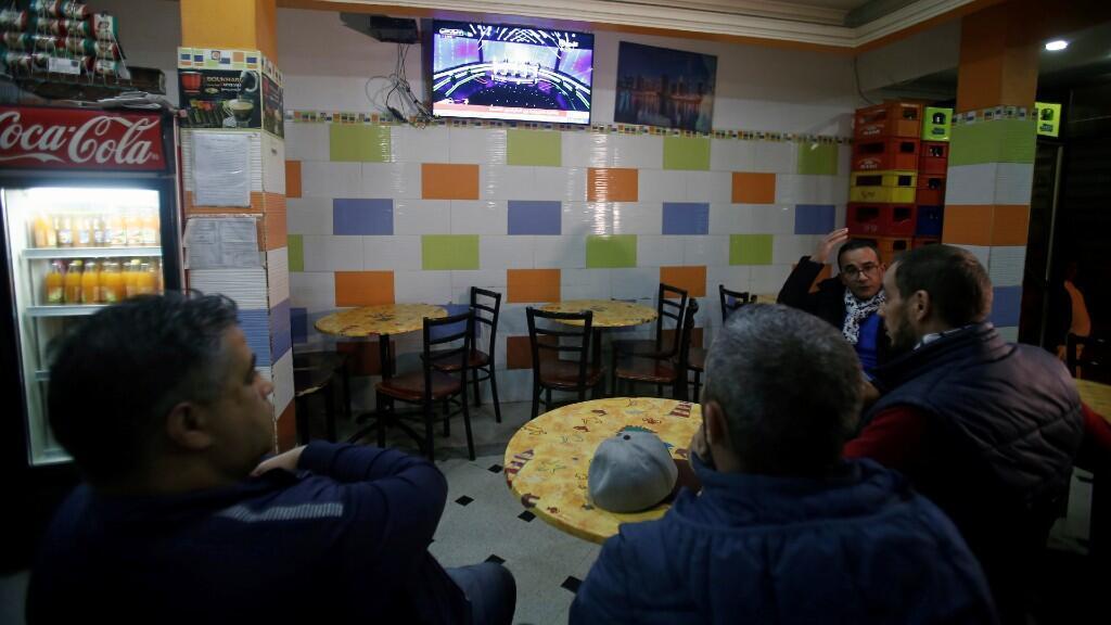 La gente mira un debate televisado entre candidatos presidenciales, antes de las elecciones del 12 de diciembre, en un café en Argel, Argelia, 6 de diciembre de 2019.