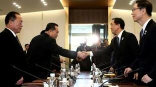 وزير كوريا الجنوبية لإعادة التوحيد شو ميونغ غيون (يمين) يصافح رئيس وفد كوريا الشمالية ري سون غوون (يسار) خلال لقاء الوفدين في بونمونجوم في المنطقة المنزوعة السلاح بين الكوريتين في 9 كانون الثاني/يناير 2018