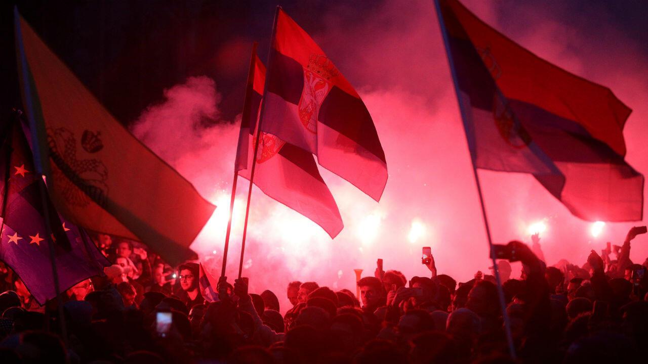 Decenas de manifestantes encendieron bengalas durante las protestas contra el presidente serbio, Aleksandar Vucic, que se llevaron a cabo ante la sede del Parlamento en Belgrado el 13 de abril de 2019.