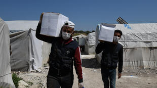 Volunteers deliver aid at a camp for displaced Syrians near the town of Deir al-Ballut, by the border with Turkey, in Syria's Afrin region in the northwest of the rebel-held side of the Aleppo province on April 14, 2020 during the coronavirus pandemic.