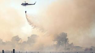 Un hélicoptère largue de l'eau sur un incendie à Butte County, en Californie, le 10 juillet 2017.