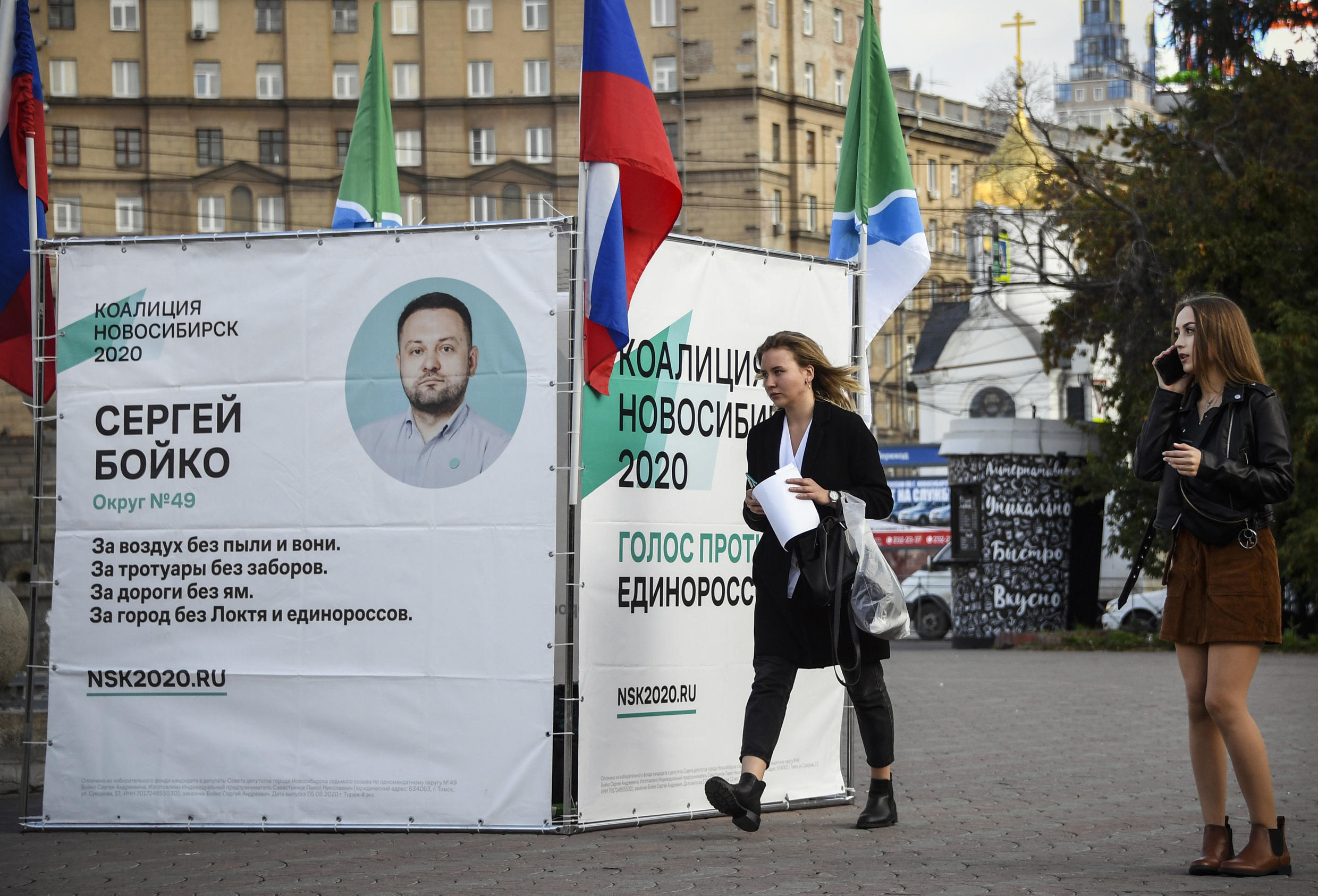 People walk past a campaign tent of Sergei Boiko, the head of Alexei Navalny's Novosibirsk headquarters and the city council candidate in September 13 regional elections, in Novosibirsk on September 9, 2020.