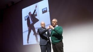 Le photojournaliste turc Burhan Ozbilici (droite) monte sur l'estrade pour la remise de son prix World Press Photo.