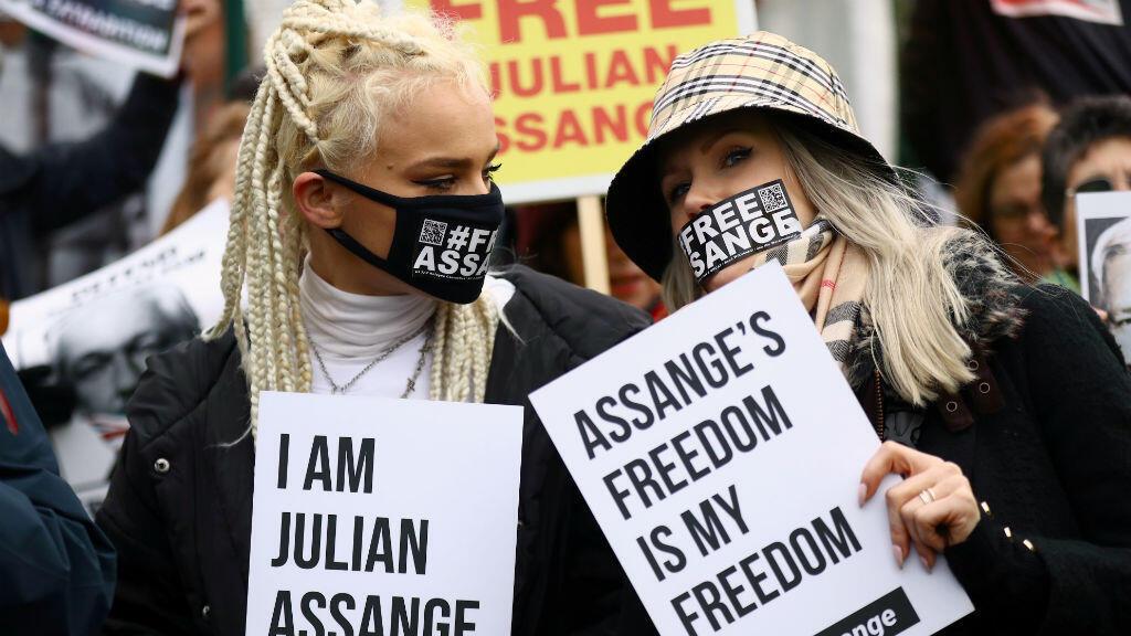 Un grupo de mujeres, vestidas con una máscara con el hashtag de apoyo para el fundador de WikiLeaks, sostienen letreros afuera de Woolwich Crown Court en Londres, Gran Bretaña, el 24 de febrero de 2020.