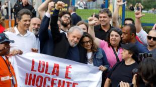 """El expresidente de Brasil, Luiz Inácio Lula da Silva, hace un gesto de victoria detrás de una pancarta que dice """"Lula es inocente"""" después de salir de prisión, en Curitiba, Brasil, el 8 de noviembre de 2019."""