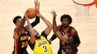 L'ailier des Los Angeles Lakers, Anthony Davis, est accroché par John Collins des Atlanta Hawks, lors de leur match de NBA, le 1er février 2021 à Atlanta