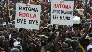 Des spectateurs brandissant des pancartes saluant la fin d'Ebola en Guinée lors d'un concert à Conakry, le 30 décembre 2015.