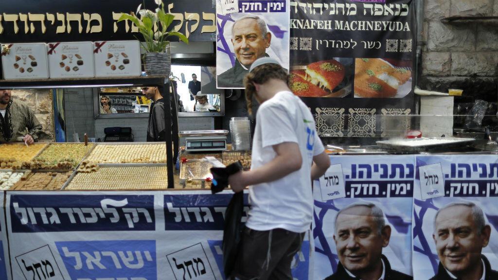 Un israelí pasa junto a carteles con el retrato del primer ministro, Benjamin Netanyahu, en el mercado de Mahané Yehudá en Jerusalén el 8 de abril de 2019, un día antes de las elecciones.