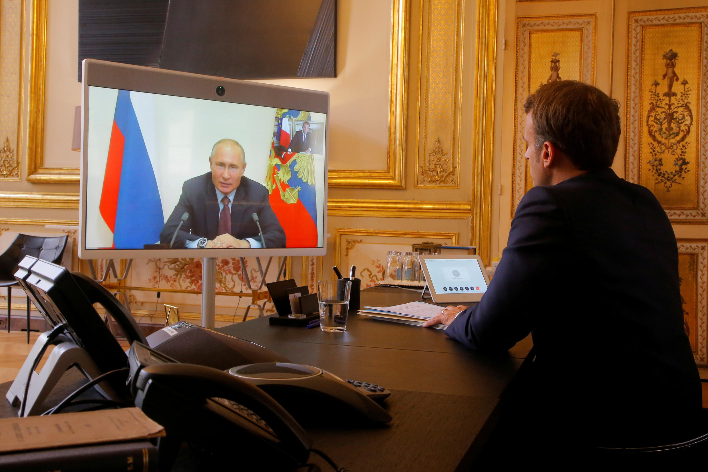 French President Emmanuel Macron listens to Russian President Vladimir Putin during a video conference at the Élysée Palace in Paris on June 26, 2020.