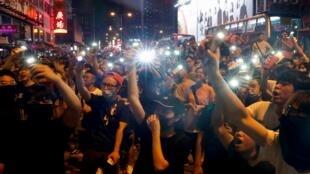 المتظاهرون يلوحون بمصباح يدوي أثناء احتجاج خارج مركز شرطة مونغ كوك في هونغ كونغ ، الصين في 7 سبتمبر/أيلول 2019.