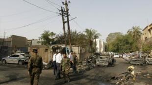 شرطيون عراقيون في موقع تفجير انتحاري في بغداد السبت 29 نيسان/أبريل 2017 استهدف الجمعة مركزا لشرطة المرور في حي الكرادة