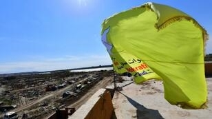 The yellow flag of the Kurdish-led Syrian Democratic Forces billows over the Islamic State group's last redoubt of Baghouz after the jihadist black flag is finally torn down