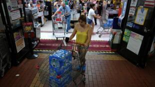 Una mujer compra agua embotellada en una tienda a medida que se acerca la tormenta tropical Dorian en Puerto Rico.