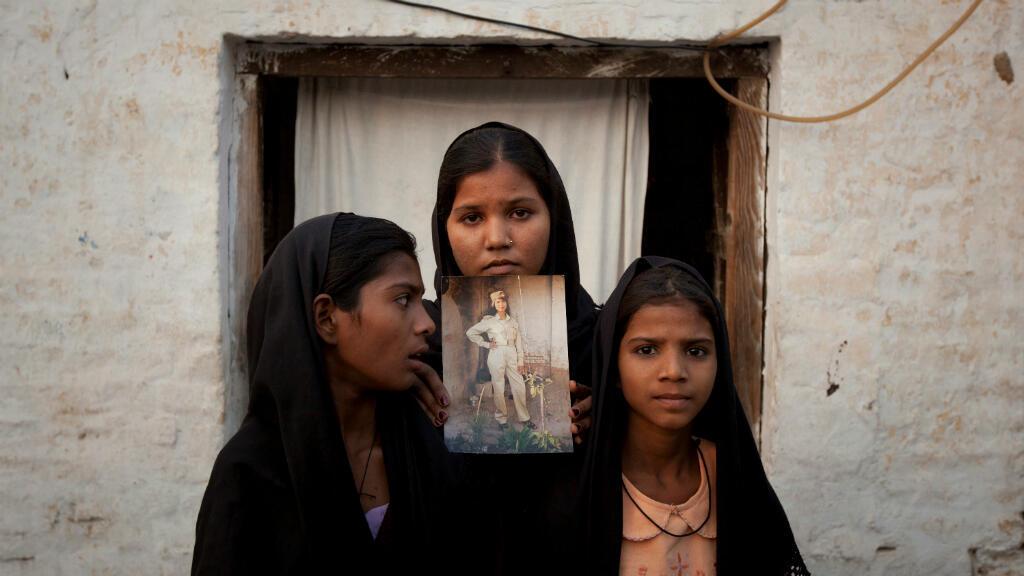 Foto de archivo: las hijas de la mujer cristiana pakistaní Asia Bibi posan con una imagen de su madre mientras se encuentran fuera de su residencia en Sheikhupura, ubicada en la provincia de Punjab de Pakistán el 13 de noviembre de 2010.