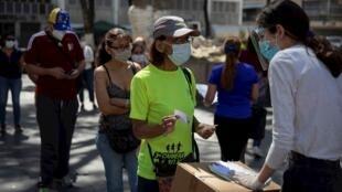 Una mujer valida su código de votación digital durante la jornada votación presencial de la consulta popular impulsada por el opositor Juan Guaidó hoy, en Caracas (Venezuela).