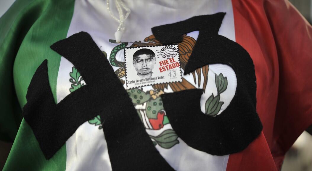 Archivo-Protesta en el marco del quinto aniversario de la desaparición de los 43 estudiantes de la escuela de capacitación docente de Ayotzinapa, con la bandera de México y la imagen del rostro de uno de los desaparecidos. En Ciudad de México, México, el 29 de septiembre de 2019.