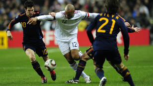 Henry (centre) is tackled during a friendly game against Spain in 2010