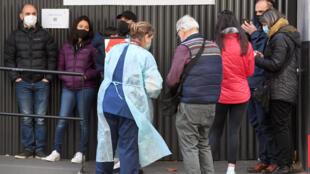Una trabajadora sanitaria habla con las personas que hacen fila fuera de un centro de detección del nuevo coronavirus en el Real Hospital de Melbourne el 16 de julio de 2020