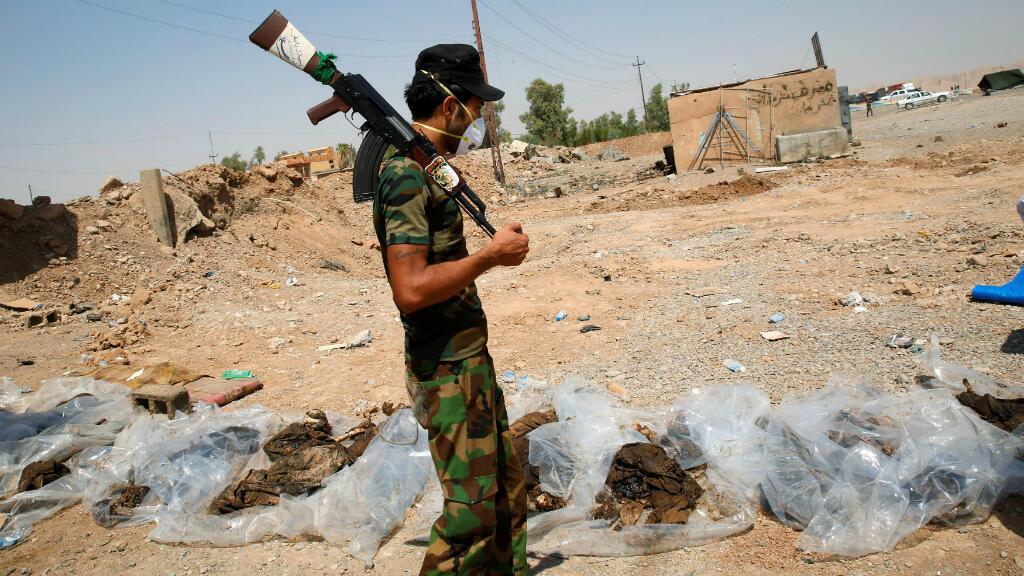 Un combatiente de la milicia china examina cuerpos recientemente desenterrados de una fosa común en las afueras de la ciudad de Sulaiman Pek, Irak, el 5 de septiembre de 2014.