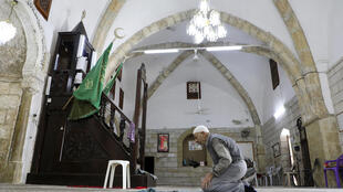 A man prays at Al-Khadra mosque in the old quarter of the West Bank town of Nablus; The Palestinian Authority has imposed a night and weekend curfew on the occupied West Bank for the next 14 days due to COVID-19