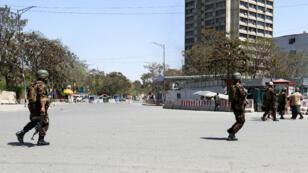 Les forces de sécurité afghanes patrouillent devant le ministère des Communications alors qu'une attaque est en cours le 20 avril 2019.