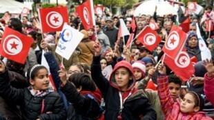 تونسيون يلوحون بأعلام بلدهم في العيد السادس للثورة على نظام زين العابدين بن علي في تجمع شعبي على جادة الحبيب بورقيبة في العاصمة تونس 14 ك2/يناير 2017