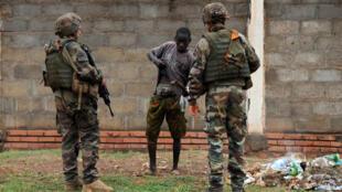 Deux soldats français de l'opération Sangaris contrôlent un jeune homme à Bangui le 27 février 2014.