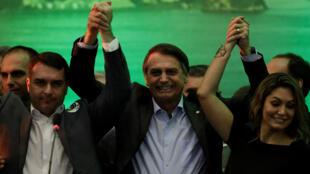 El diputado federal Jair Bolsonaro sostiene a su hijo Flavio Bolsonaro (L) y su esposa Michelle Bolsonaro durante la convención nacional del Partido para el Socialismo y la Liberación (PSL) donde se formalizará como candidato a la Presidencia de la República , en Río de Janeiro, Brasil, el 22 de julio de 2018.