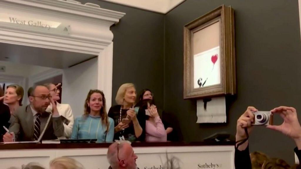 """Captura de pantalla del vídeo que muestra el momento en que la obra """"Girl with Ballon"""" es dañada en público por su autor."""