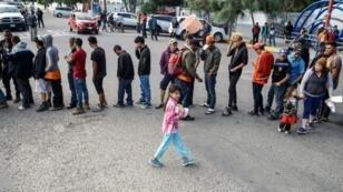 مهاجرون من أمريكا الوسطى يقفون في طابور لتسلم مواد غذائية في تيخوانا في المكسيك على الحدود مع الولايات المتحدة في 15 نوفمبر 2018