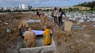 أفراد من طاقم لدفن الموتى تابع لبلدية تونس يدفن جثمان متوف بكوفيد-19 في مقبرة الجلاز في 11 شباط/فبراير 2021