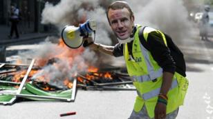 Un manifestant porte un masque à l'effigie du président Emmanuel Macron, le 20avril2019, lors de l'acteXXIII des Gilets jaunes.