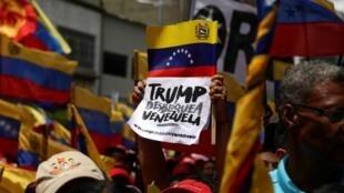 """Un letrero dice """"Trump desbloquea Venezuela"""" en una manifestación para conmemorar el Bicentenario de la Batalla de Boyacá en el Panteón Nacional en Caracas, Venezuela 7 de agosto de 2019."""